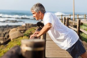 middle-aged man exercising by the beach